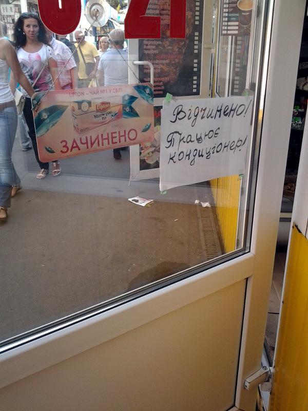 Две таблички рядом: «Зачинено», «Відчинено! Працює кондиціонер!»